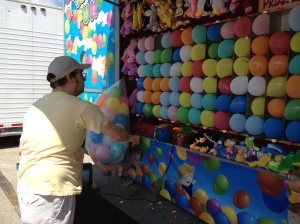 My sister's fiance tries to win a tie-dye dolphin at the Balloon Pop game in the Midway.