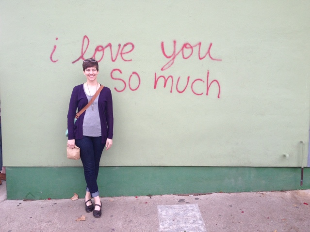 Aw, I love you, too! Caitlyn poses in front of an iconic piece of street art on South Congress.